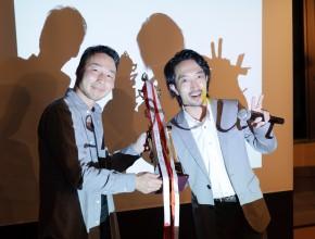 優勝した青工逢山の工藤さんに、前々回優勝の菅野さんからトロフィーを授与。